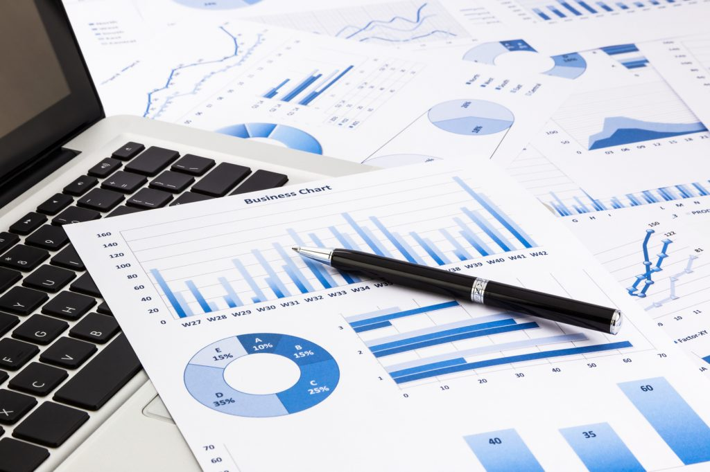 laptop and pen with blue business charts, graphs, statistic and documents background for education and business concepts